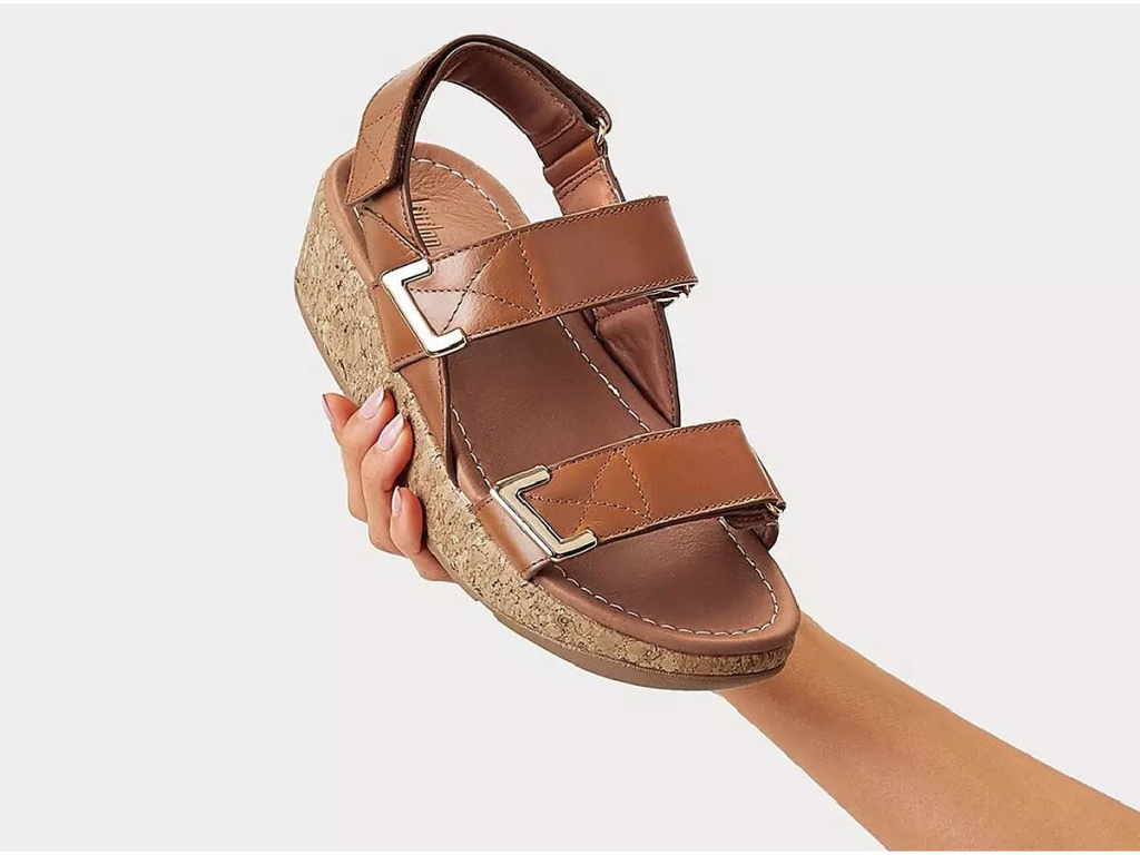 hand holding up brown sandal