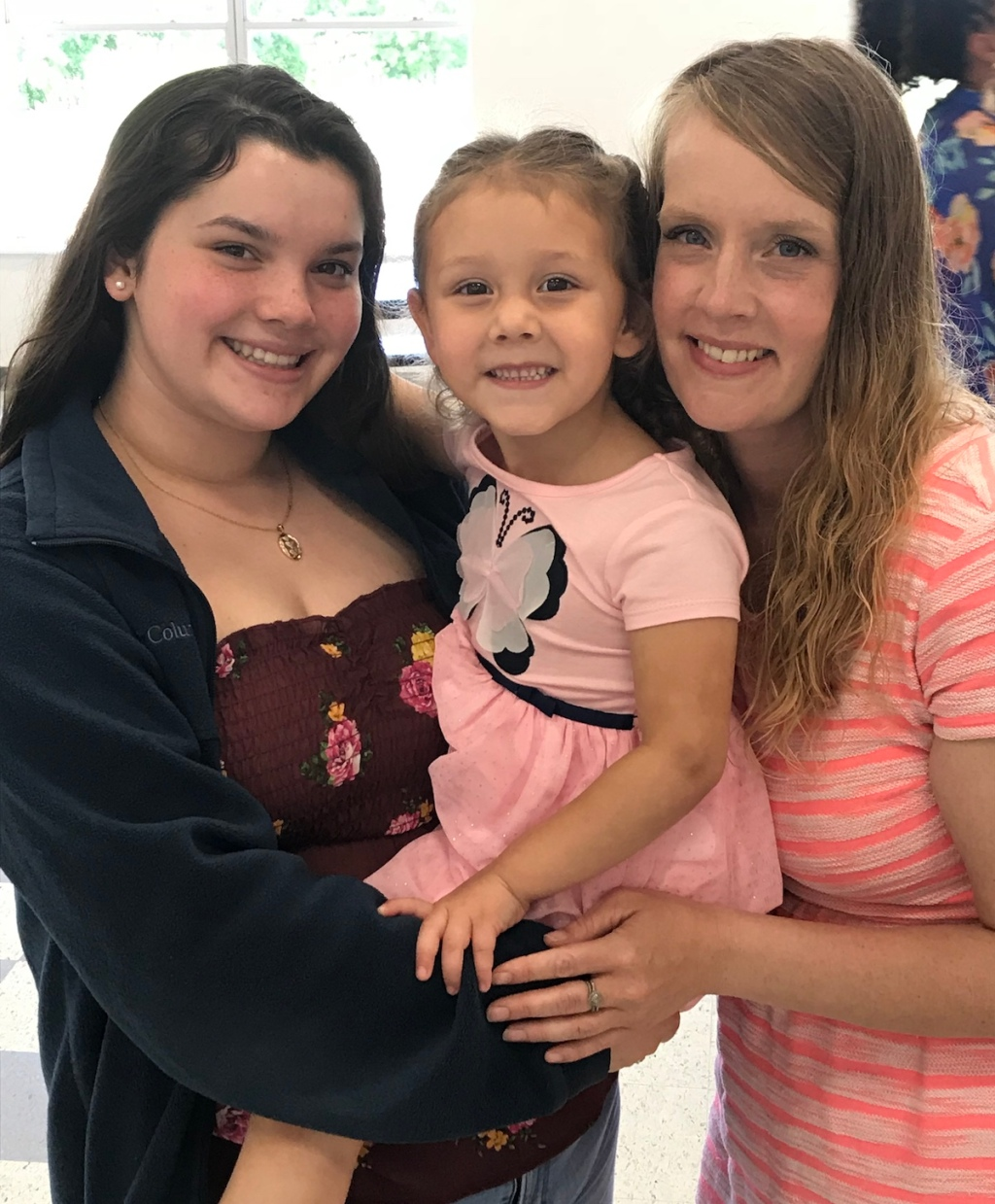 two woman holding young girl smiling at camera