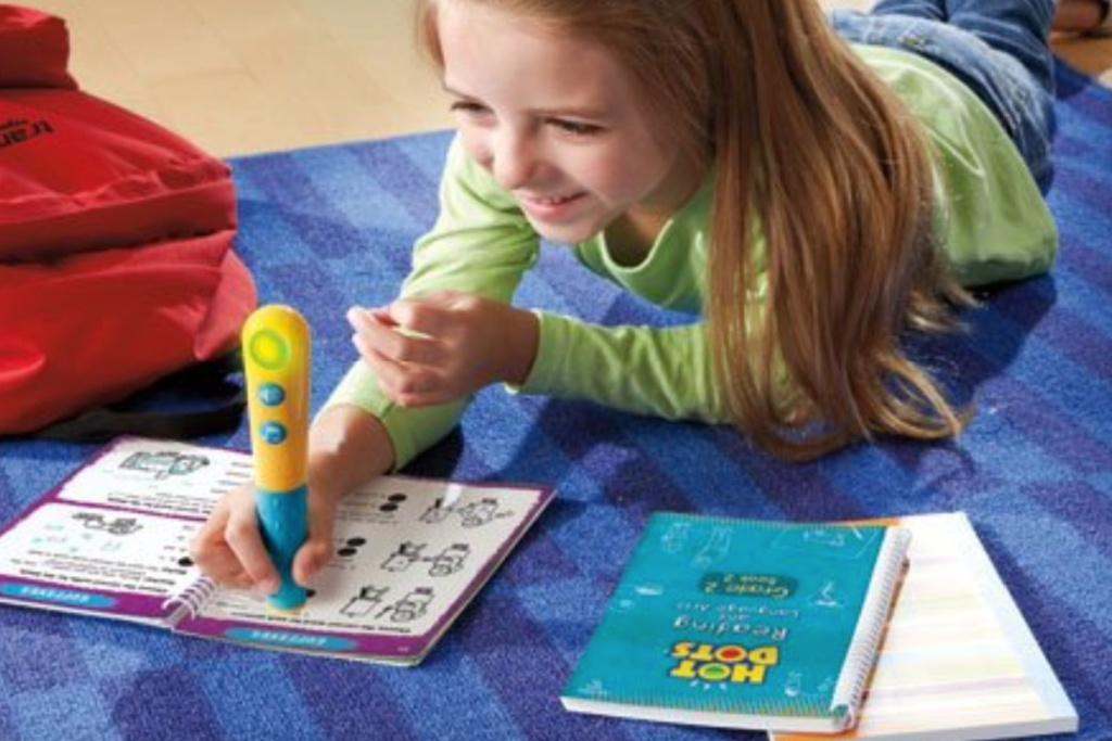 girls reading on floor w/ hot dots reading activity