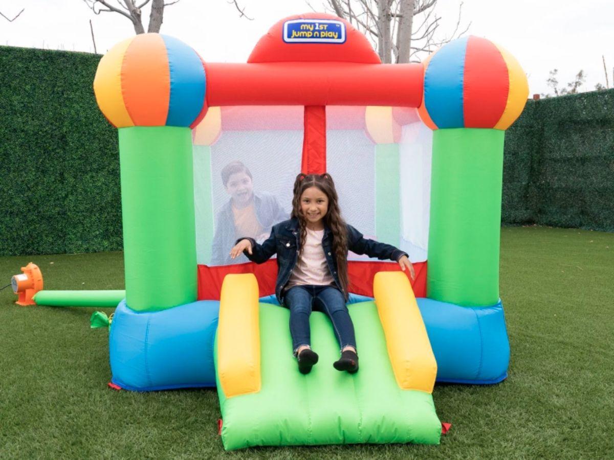 girl sliding down inflatable slide