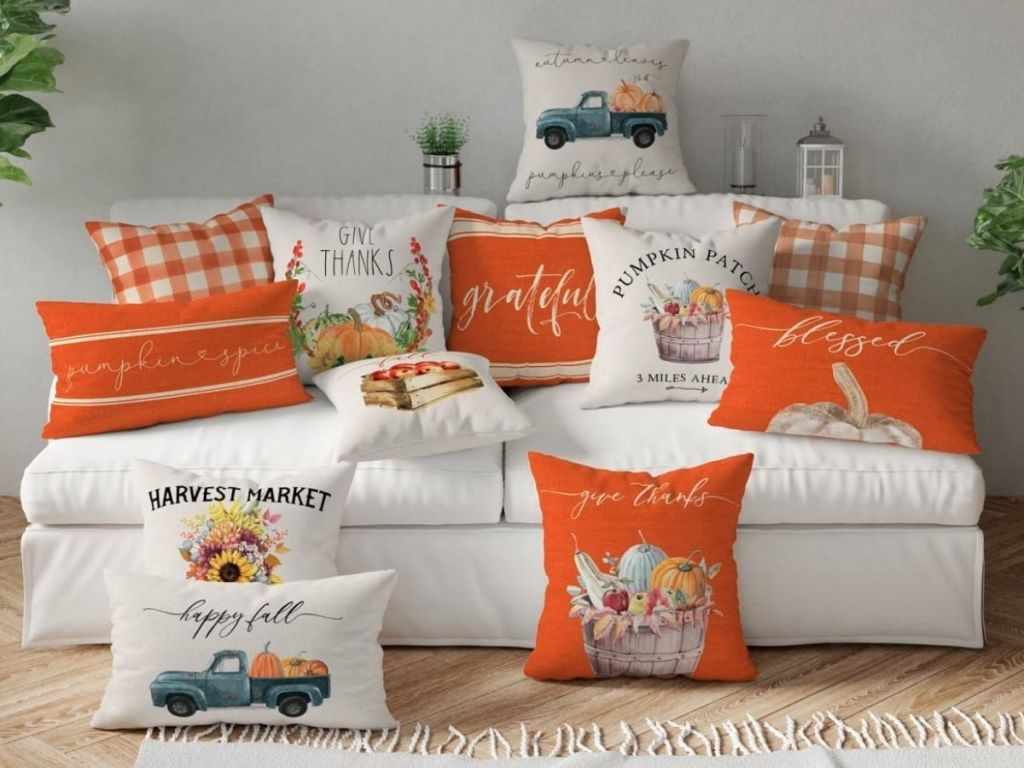 different Autumn themed pillow covers on pillows scattered on white couch