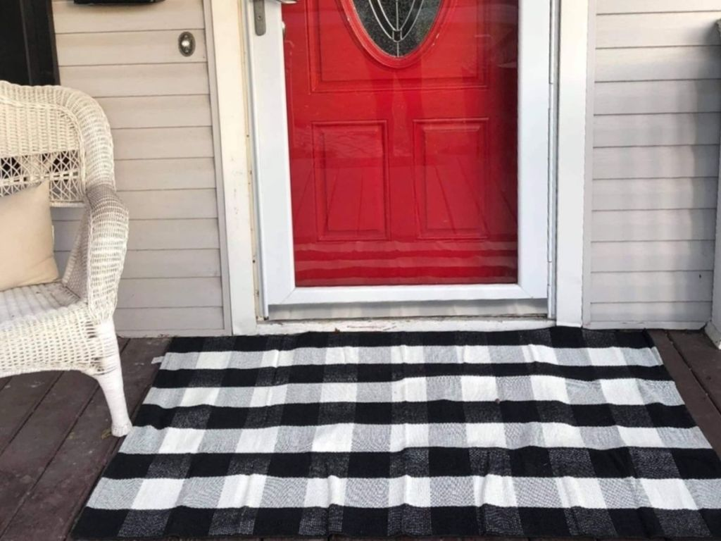 black and white buffalo check rug in front of door on porch