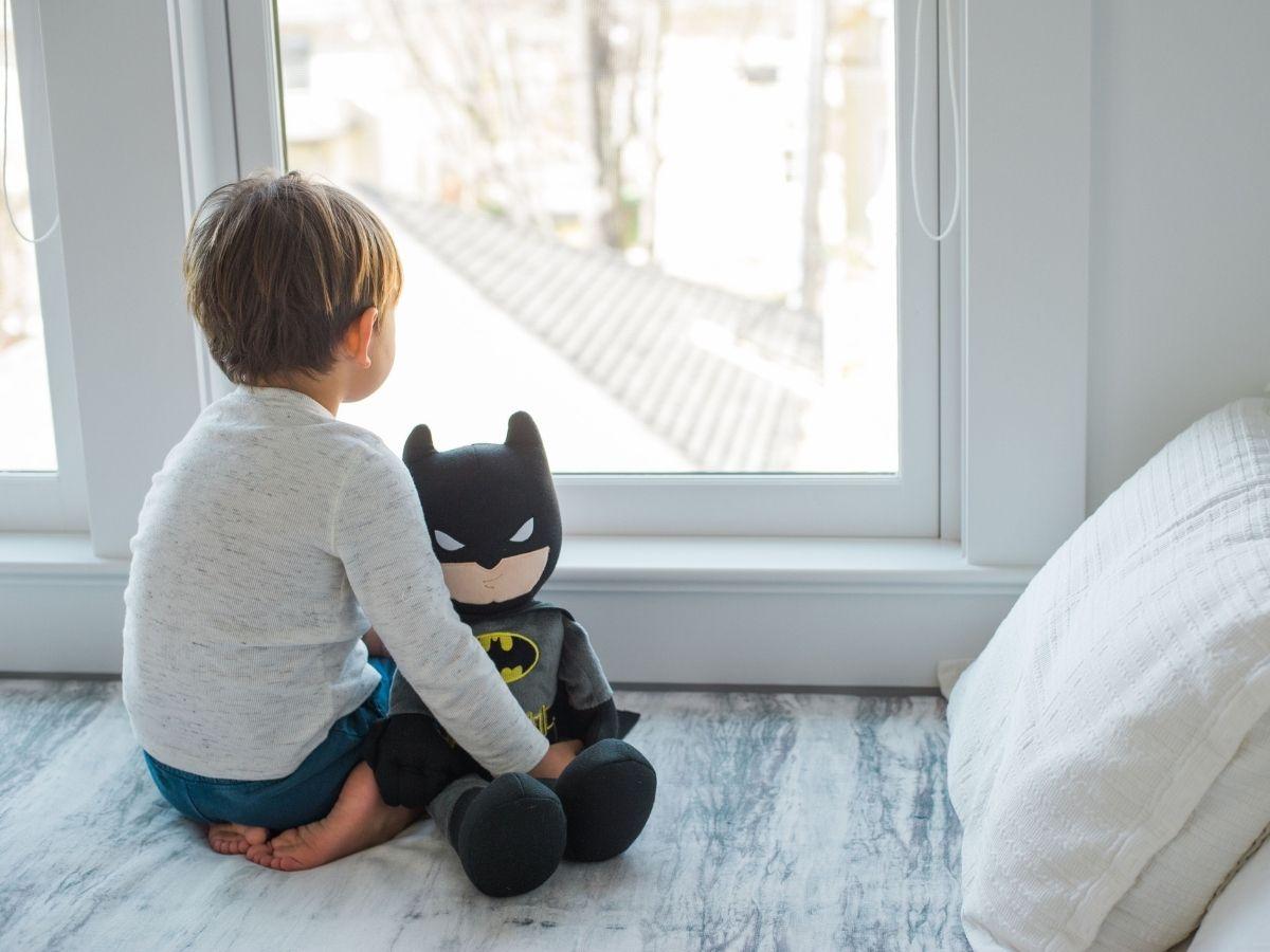 boy holding batman plush DC characters