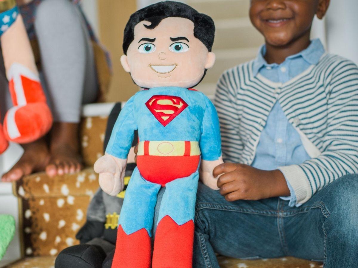 kid holding plush superman