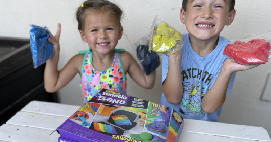 kids holding bags of kinetic sand