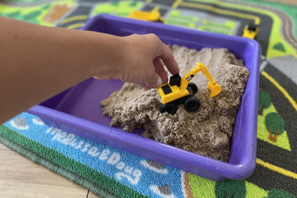 hand driving in kinetic sand construction pit