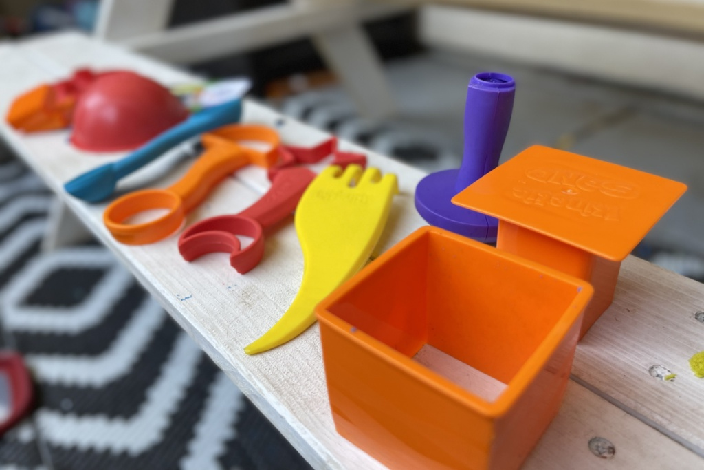 many kinetic sand tools lined up on a bench