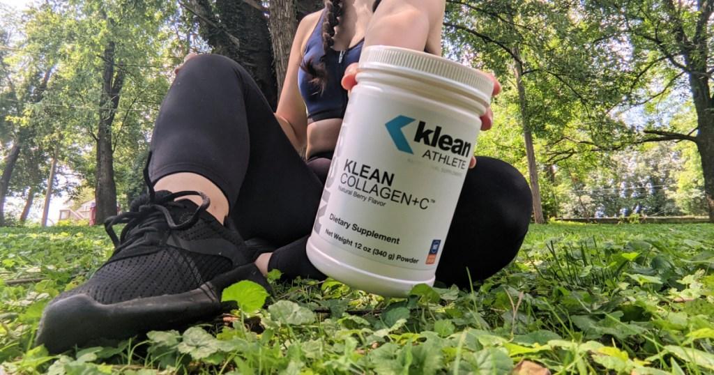 woman sitting on ground holding collagen + vitamin c powder
