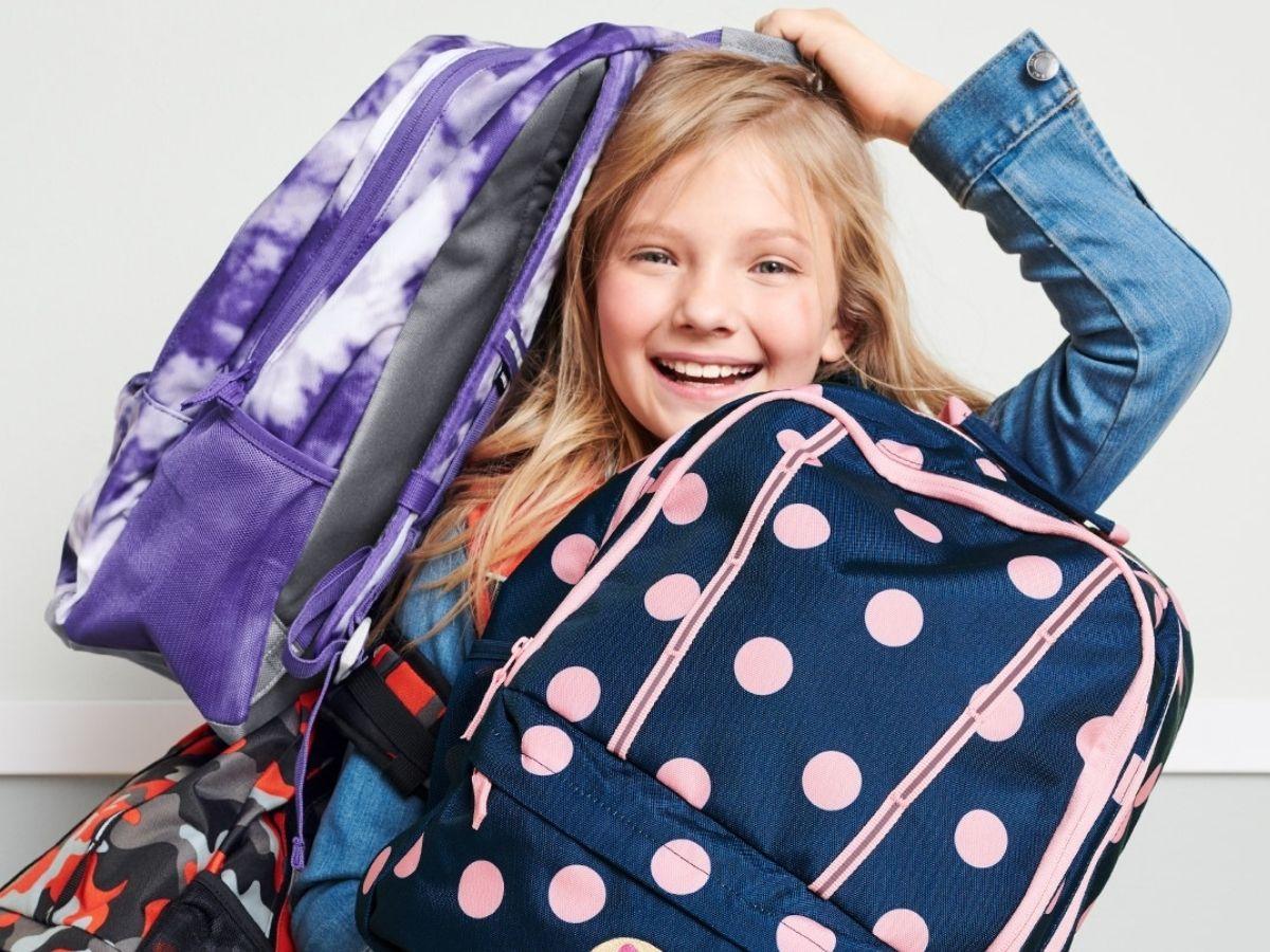 girl holding different backpacks