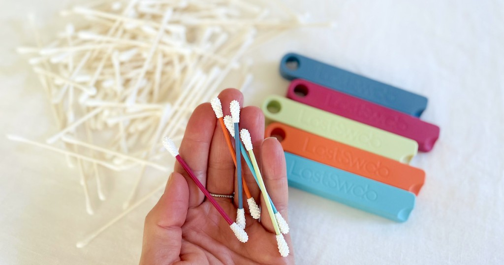 hand holding colorful qtips over pile of white ear swabs