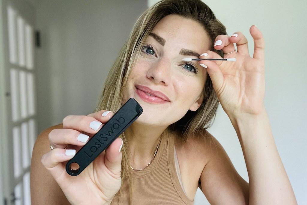 woman holding q tip on eye showing off black last swab case