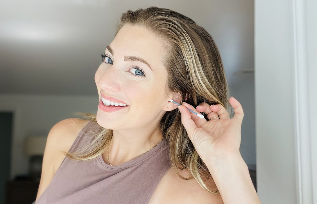 woman putting q-tip in ear smiling at camera