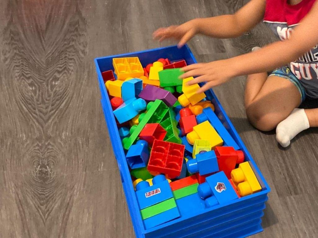kid putting legos in lego box