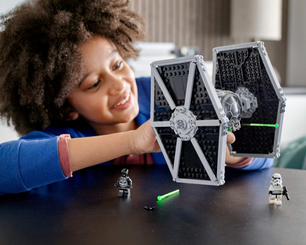 boy playing with lego tie fighter