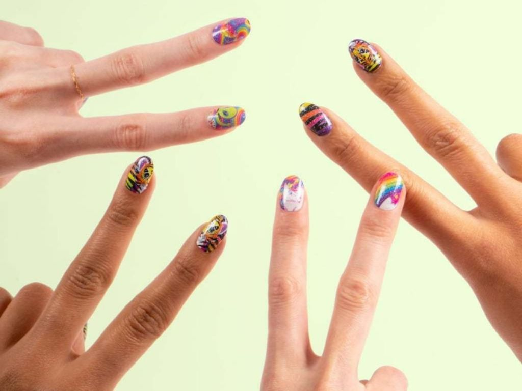 hands giving peace sign with designs on nails