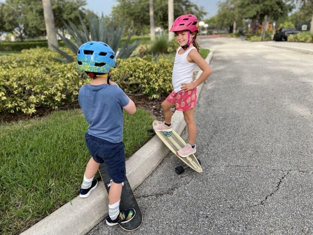 girl and boy wearing helmets skateboarding