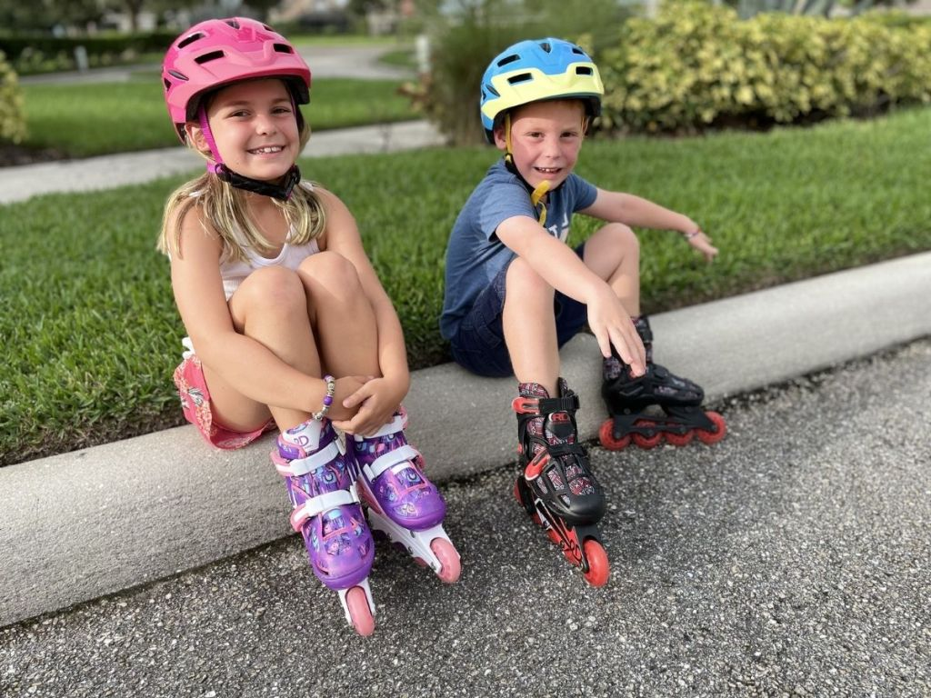 girl and boy wearing helmets and roller blades sitting on curb