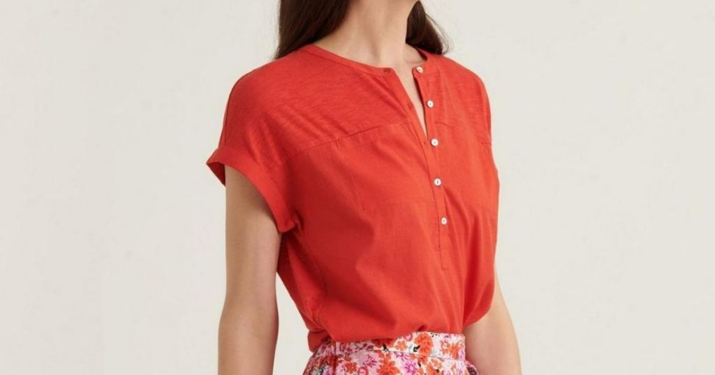 woman wearing red button down short-sleeve top