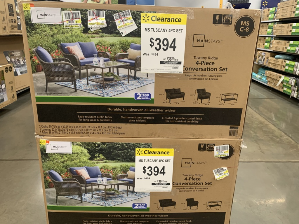 2 boxes with outdoor patio sets in them on store showroom floor