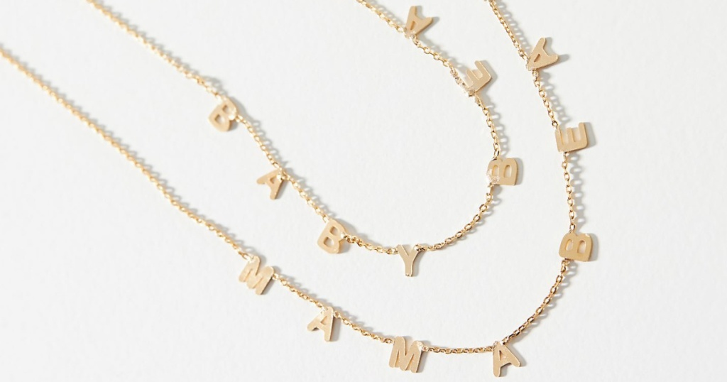 two gold necklaces with letters on it