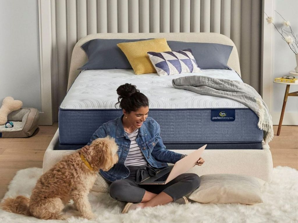 woman sitting in front of bed with dog