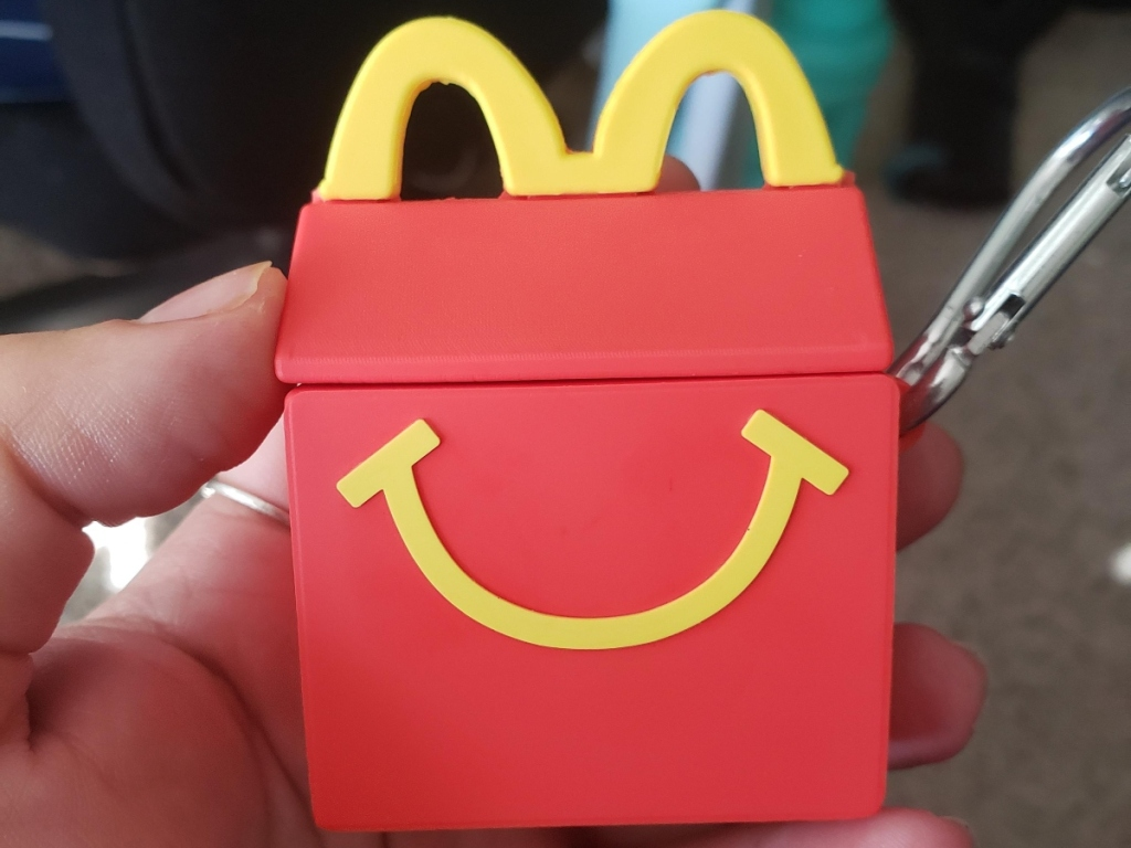 holding an AirPods case shaped like a Happy Meal