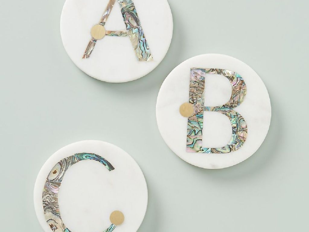 three coasters sitting on counter with letters on them
