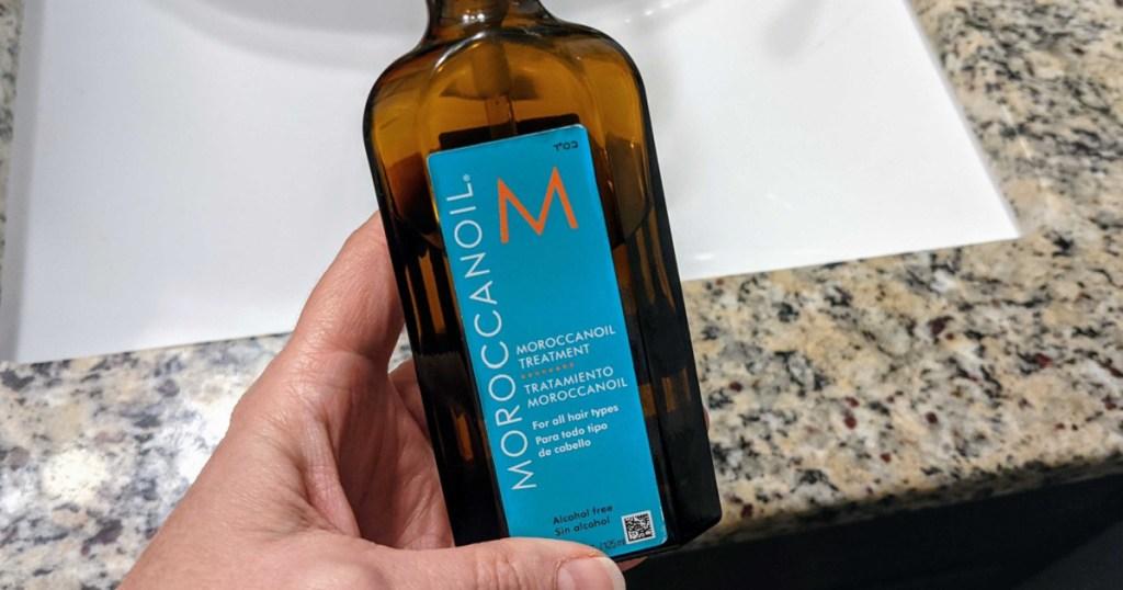 hand holding bottle of hair oil in bathroom