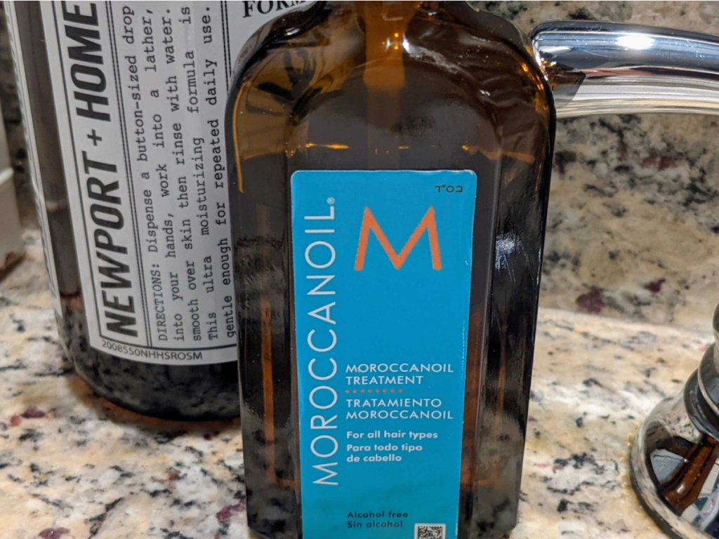 bottle of hair oil on bathroom sink counter