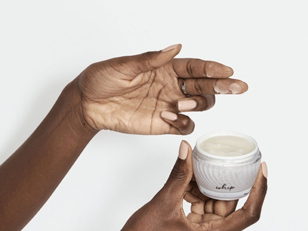 finger grabbing face cream from container