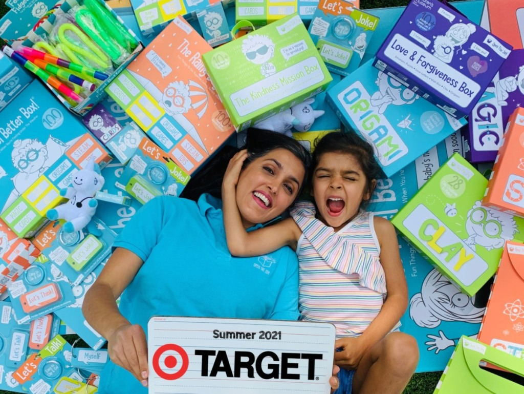 woman and child on pile of Open the Joy products