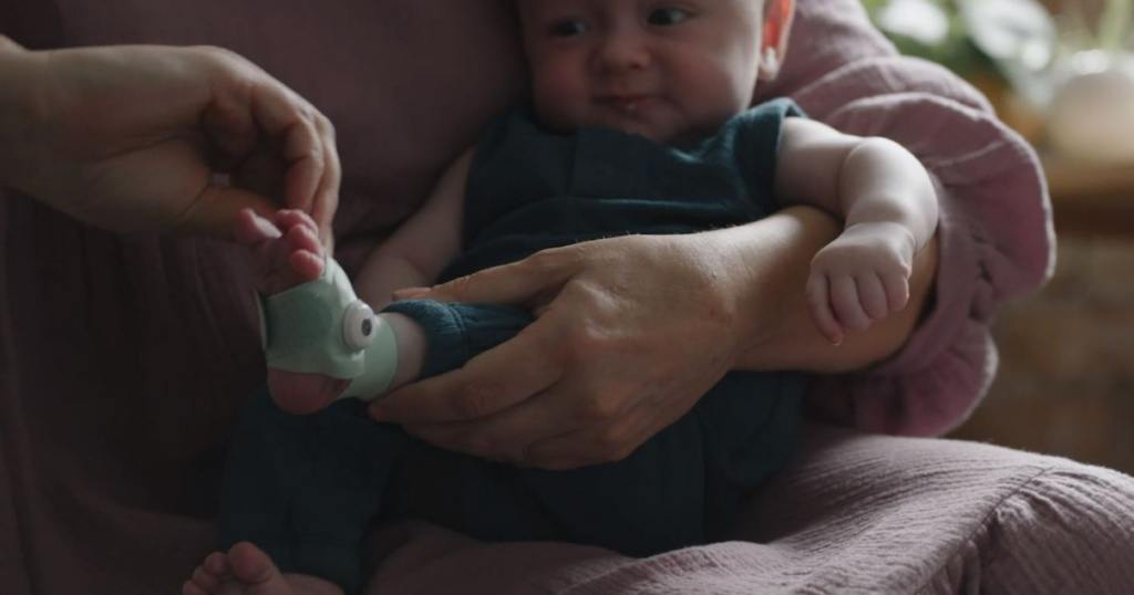 person holding baby and putting sock on him
