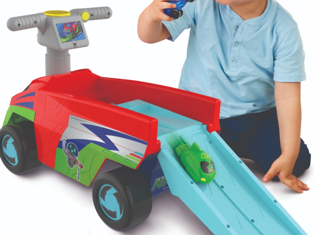 child playing next to plastic car with track
