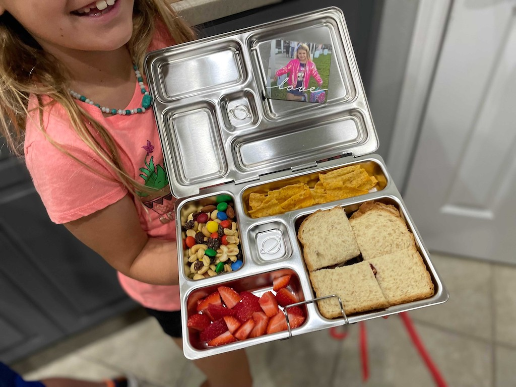 little girl holding Planetbox metal bento style lunch box
