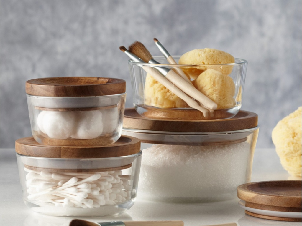 glass bowls with wooden lids containing make up products