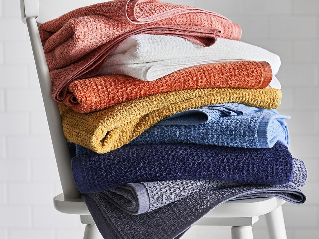 white chair with stack of colored towels on it