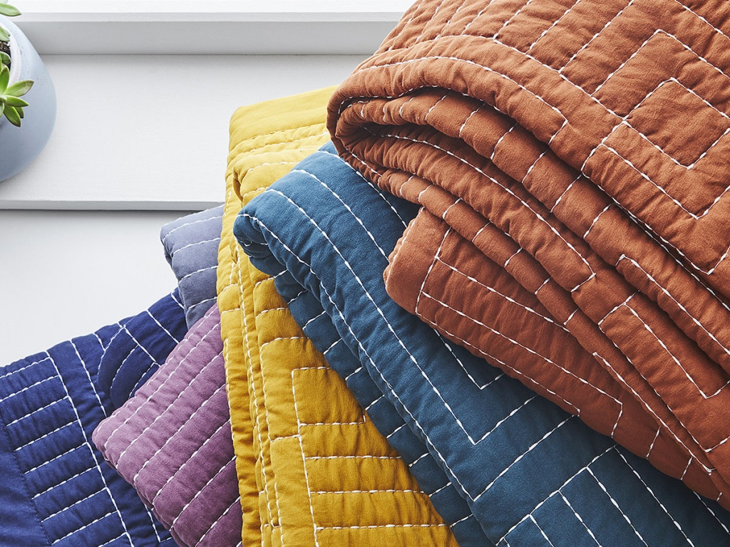 several brightly colored quilts folded in pile