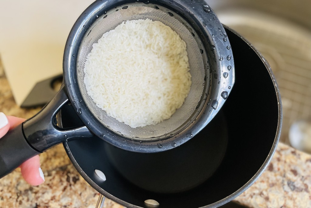 strainer with wet rice inside over empty pot