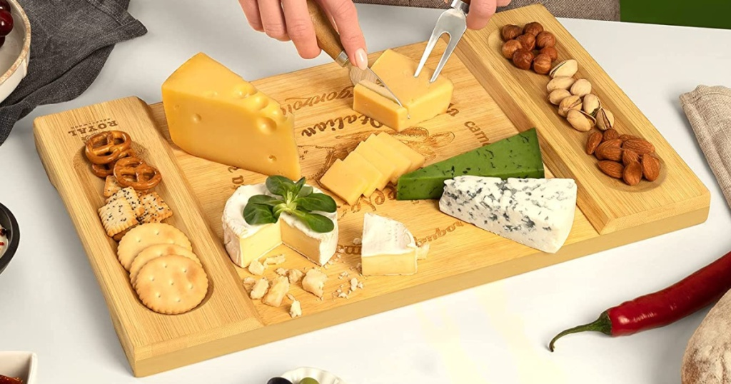 person slicing a piece of cheese on a charcuterie board with other cheeses and crackers