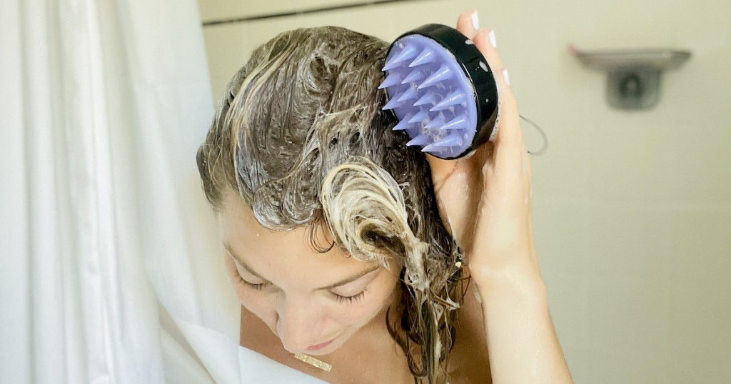 woman holding scalp massager in shower with soapy hair