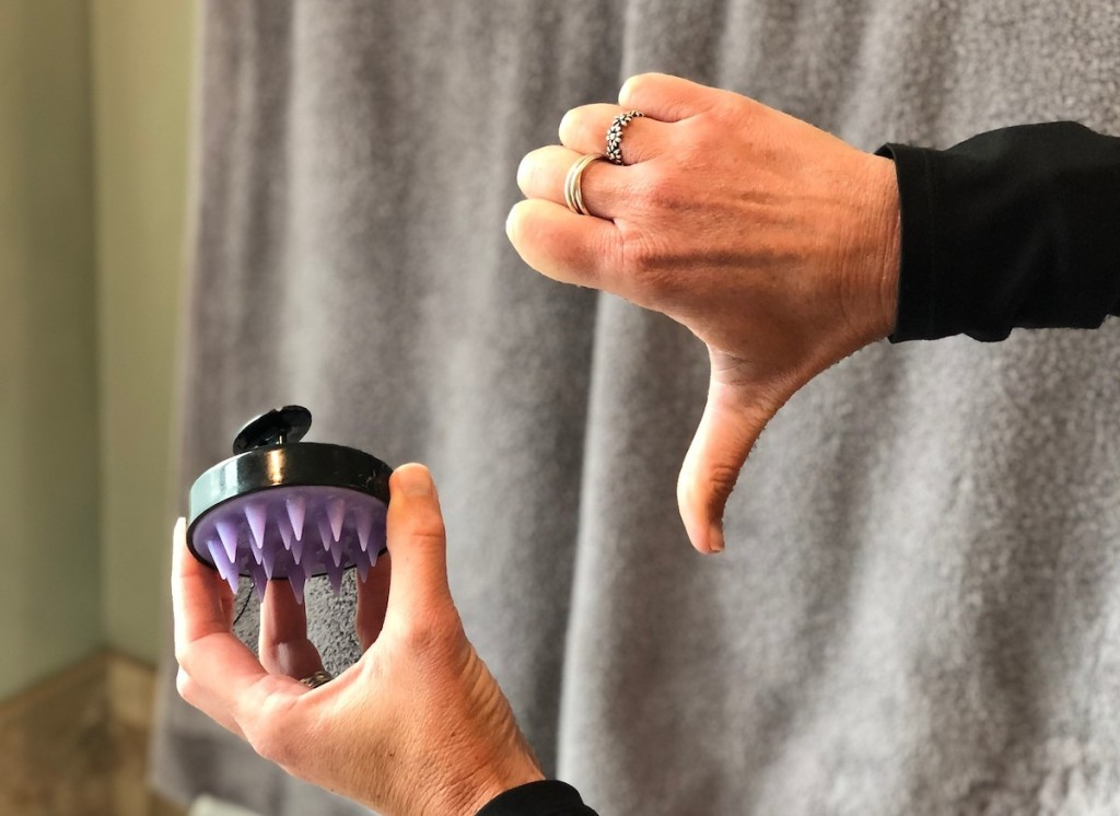 hand holding scalp massager giving thumbs down