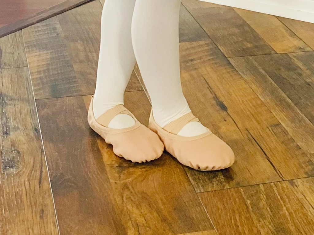 girl wearing white tights and pink ballet shoes