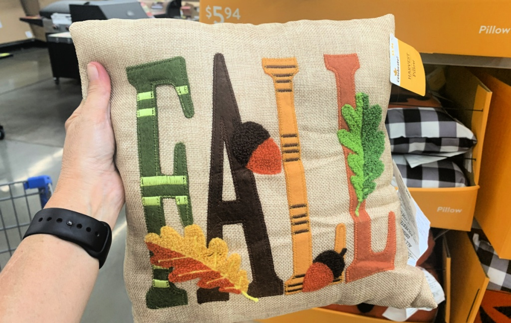 hand holding up a pillow that has the word fall