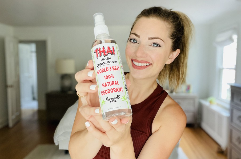 woman holding up bottle of thai crystal deodorant