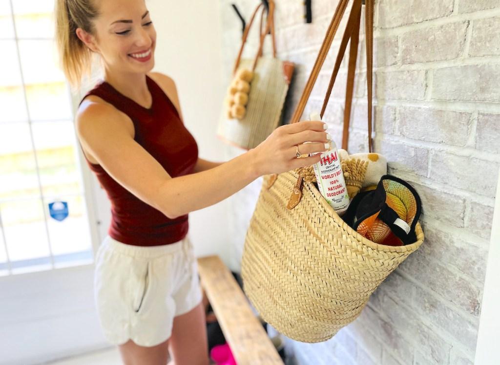 woman putting thai crystal deodorant in beach tote bag hanging on brick wall