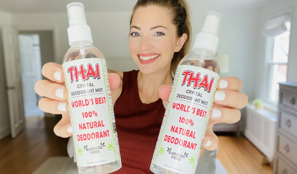 woman smiling holding two bottles of thai crystal deodorant mist