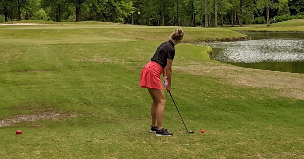 woman golfing in red skirt