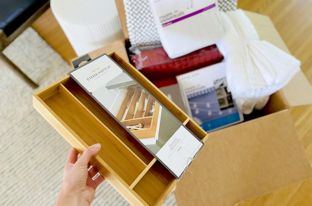 hand holding bamboo utensil organizer over open box