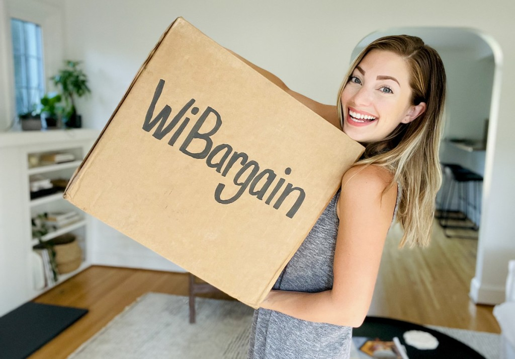 woman holding brown box with wibargain on front