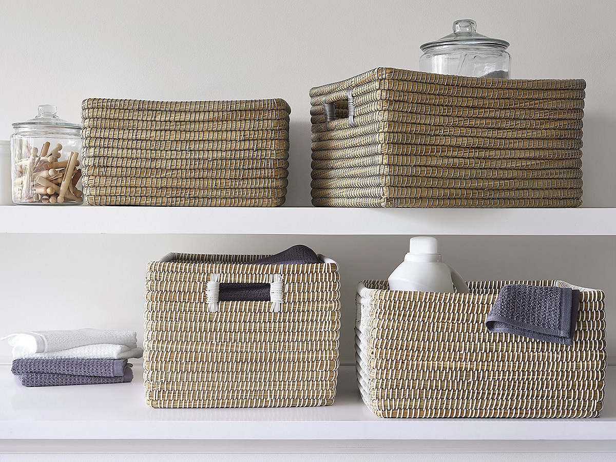 2 white shelves with baskets packed with laundry supplies on them